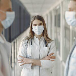 Zwei Mediziner stehen sich gegeüber und im Hintergrund eine weitere Medizinerin mittig guckt in die Kamera.
