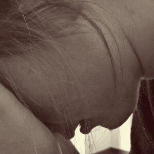 Eine verzweifelte Frau hält ihr Gesicht in den Händen.